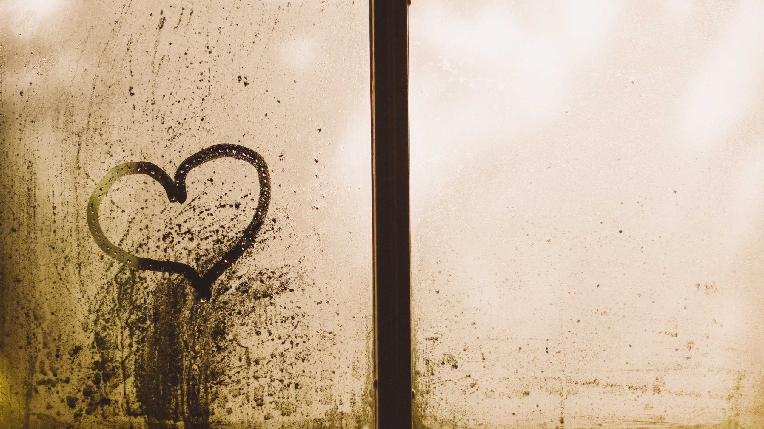 A heart drawn on a stained window pane.