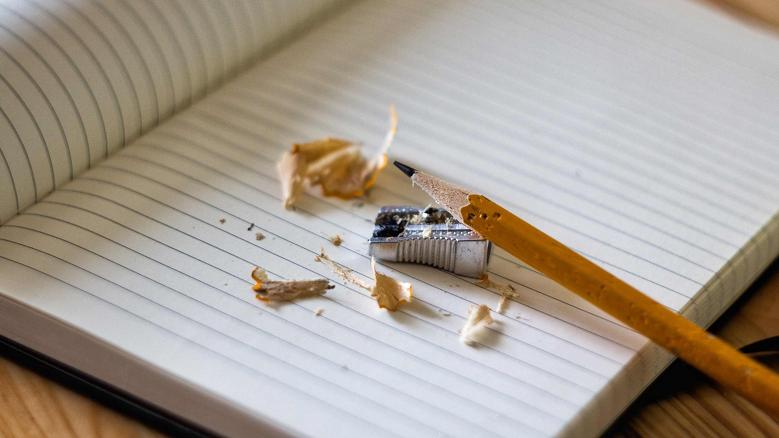 A pencil resting on a notebook, being sharpened.
