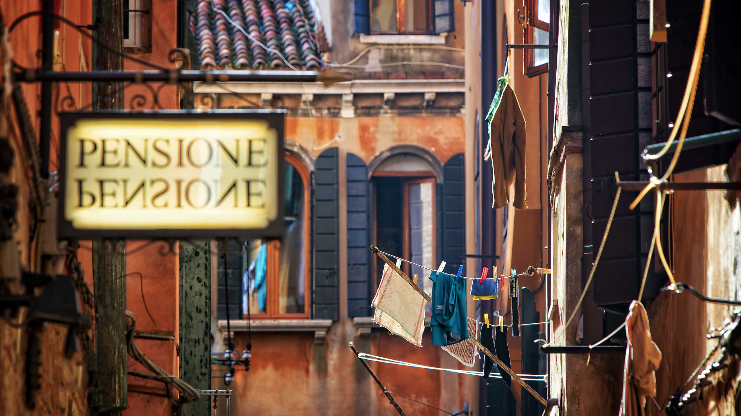 A sign of a pensione in an alley.
